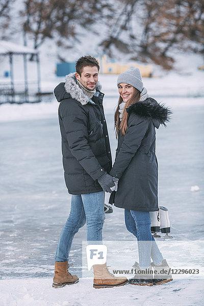 Volle Länge des glücklichen Paares  das über die Schulter schaut  während es auf der Eisbahn steht.