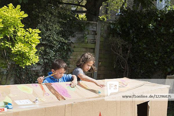 Multi-ethnische Freunde malen Pappspielhaus im Hinterhof an einem sonnigen Tag