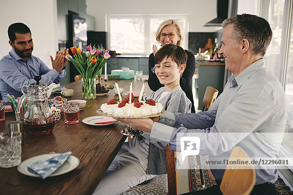 Smiling boy with grandparents and father with birthday cake at table