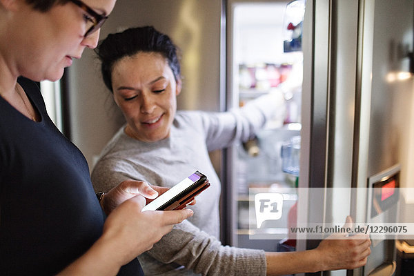 Woman showing mobile phone while girlfriend opening refrigerator in kitchen