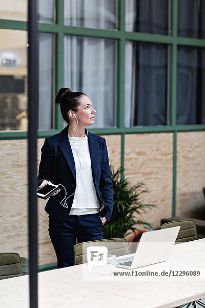 Businesswoman talking through headphones on mobile phone by table at office