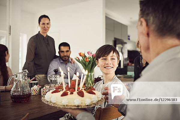 Smiling boy looking at grandfather holding birthday cake with family in party