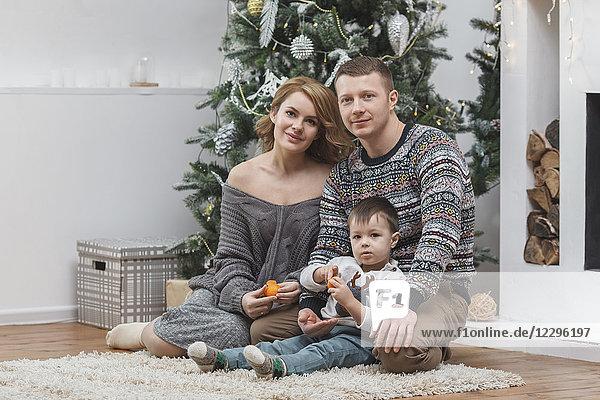 Porträt von Vater und Mutter sitzend mit Sohn auf einem Teppich am Weihnachtsbaum zu Hause