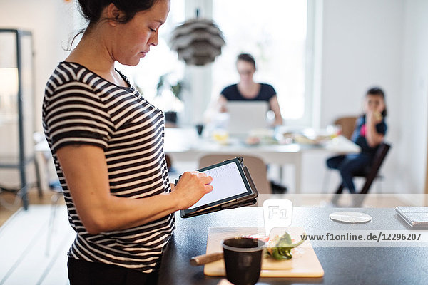 Woman making food while using digital tablet at kitchen with family in background