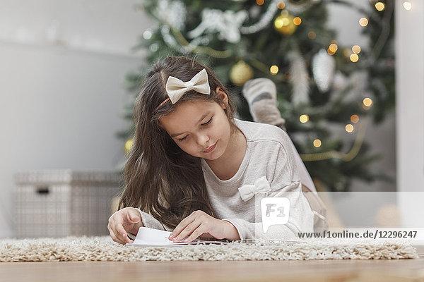 Mädchen liegt auf dem Teppich und liest zu Hause Buch