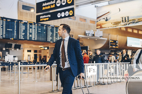 Mature businessman with luggage walking in airport terminal