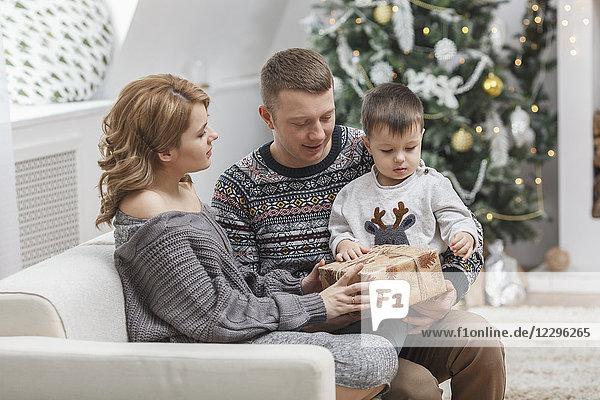 Mann schaut Frau an  die dem Sohn  der zu Hause auf dem Sofa sitzt  zu Weihnachten ein Geschenk macht.