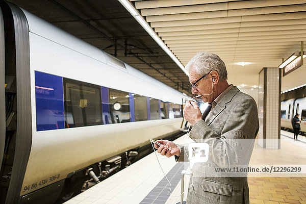 Side view of senior man talking on smart phone while standing at subway station