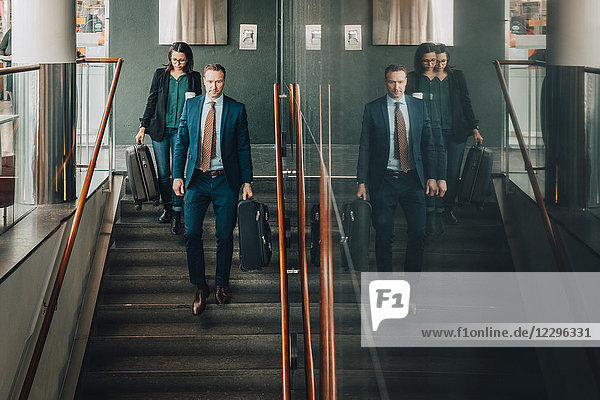 Full length of business couple moving down stairs at airport