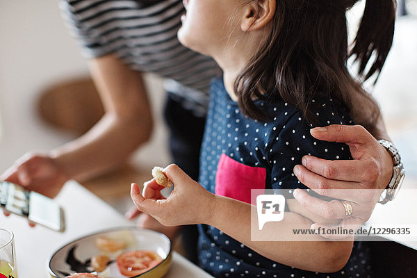 Midsection of mother embracing daughter while having breakfast at dining table