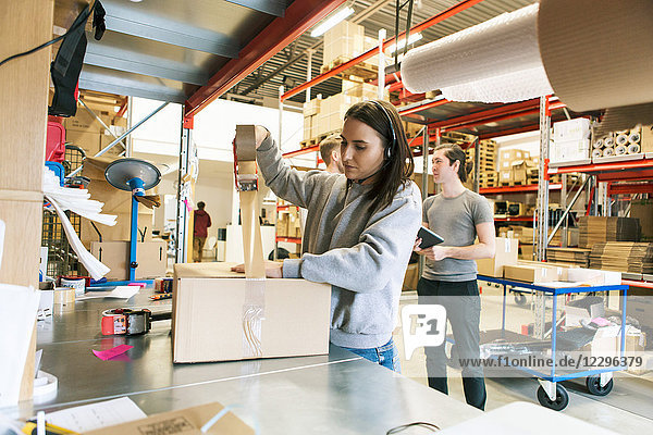 Woman packing box while coworkers discussing in distribution warehouse