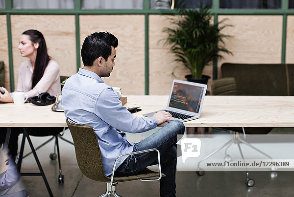 Businessman using laptop while sitting with colleague at table in office