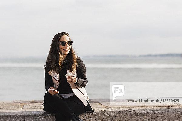 Lächelnde Frau sitzt auf einer Stützmauer mit Smartphone und trinkt gegen das Meer.