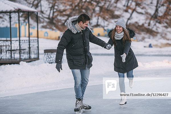 Volle Länge des glücklichen Paares  das beim Eislaufen Händchen hält.