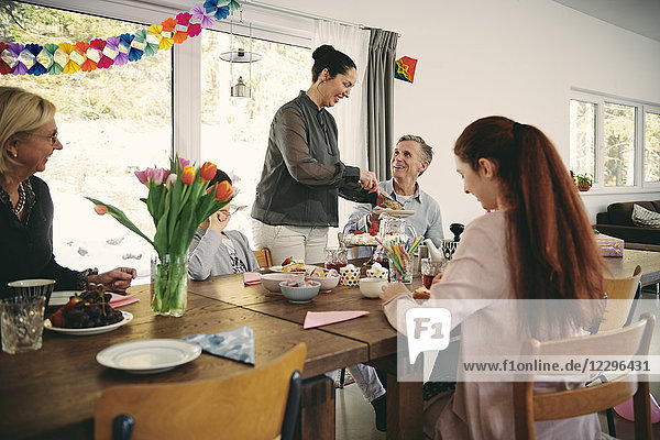 Smiling woman serving food to family during birthday party