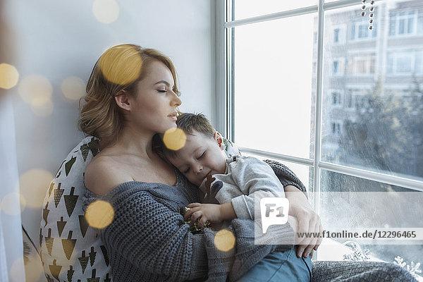 Junge Frau entspannt mit Sohn am Fenster zu Hause