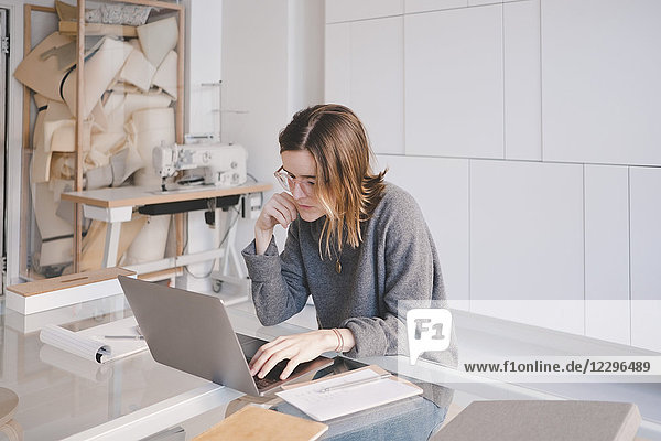 Young female fashion designer using laptop at desk in store