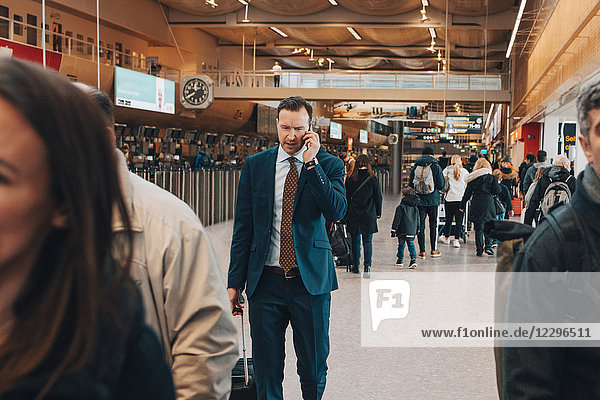 Mature businessman using mobile phone while walking with crowd in airport