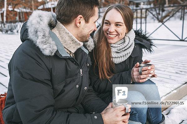 Glückliches Paar  das im Winter mit Getränken an der Strandpromenade sitzt.