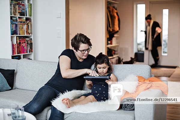 Mother showing digital tablet to daughter while sitting on sofa at home