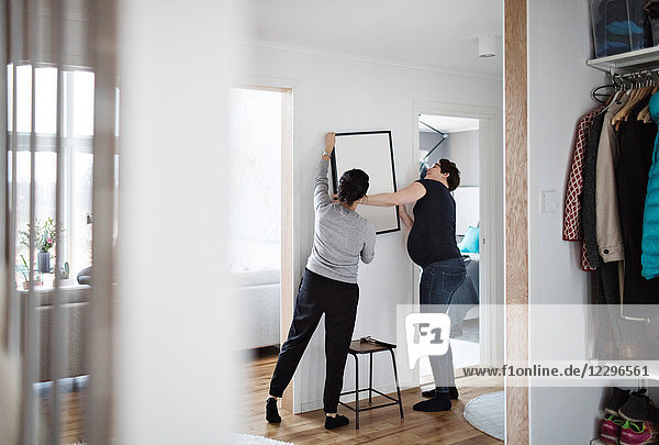 Lesbian couple arranging paintings on wall at home