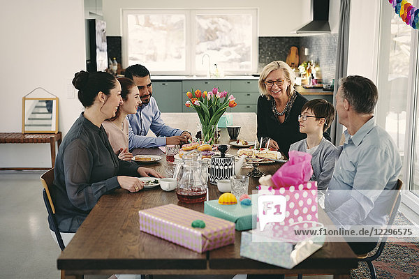 Happy multi-generation family enjoying at table during birthday party