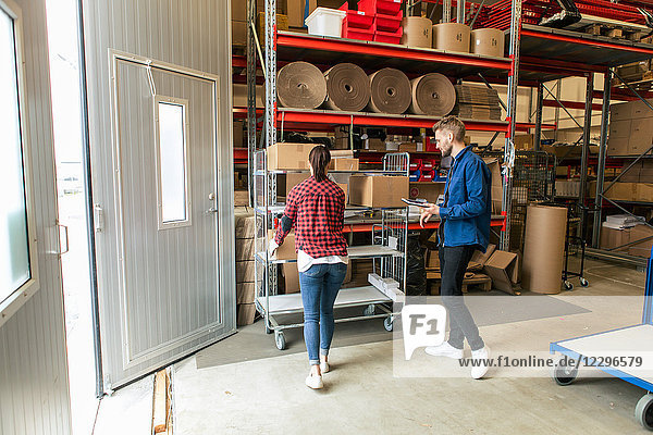 Manual worker looking at female colleague loading boxes on trolley at distribution warehouse
