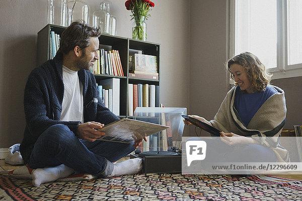 Fröhliches mittleres erwachsenes Paar sitzend mit Plattenteller auf Teppich zu Hause