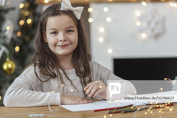 Porträt eines lächelnden Mädchens am Tisch sitzend mit beleuchteten Lichterketten