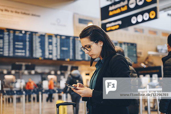 Side view of mid adult businesswoman using mobile phone in airport terminal