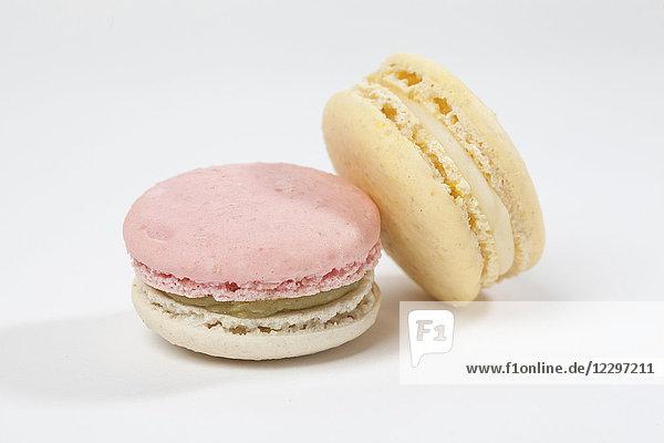 Zwei Macarons vor weissem Hintergrund (Nahaufnahme)