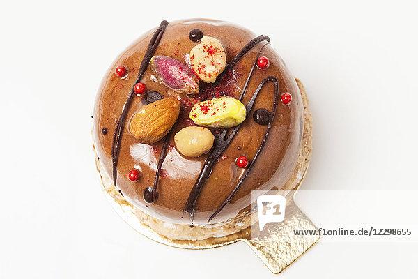 Ein großes Macaron  mit Schokolade und Nüssen verziert