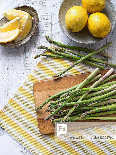 Grüner Spargel auf gestreiftem Tischset mit Zitronen