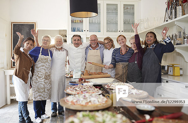 Portrait confident active senior friends and chef taking pizza cooking class
