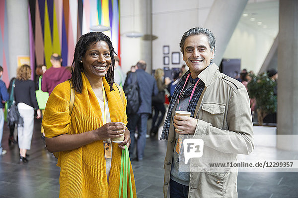 Portrait smiling  confident businessman and businesswoman drinking coffee at conference Portrait smiling, confident businessman and businesswoman drinking coffee at conference