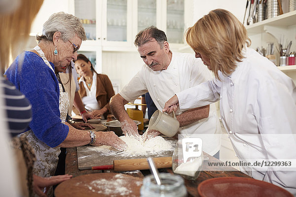 Chef and senior woman making pizza dough flour nest in cooking class