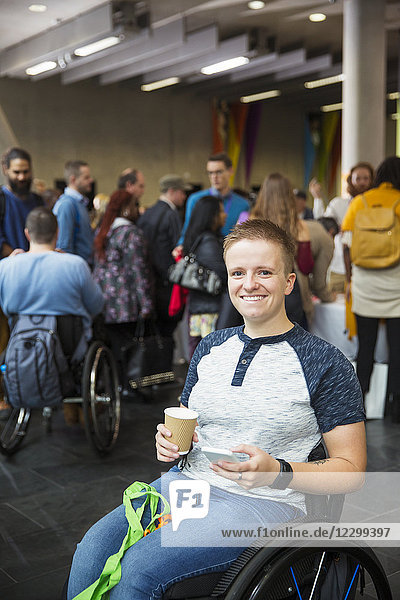 Portrait smiling  confident young woman in wheelchair drinking coffee at conference