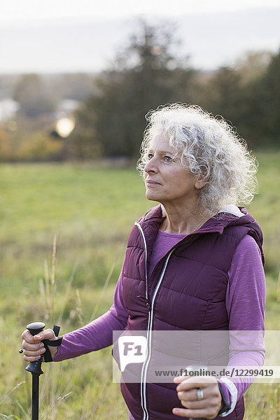 Thoughtful active senior woman hiking with poles in rural field