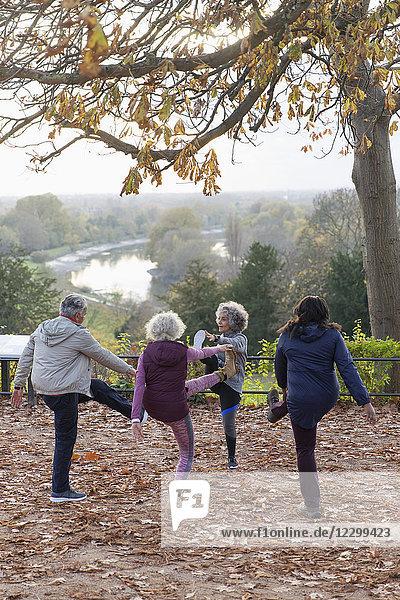 Active seniors stretching  exercising in autumn park