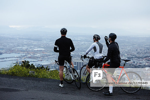Male cyclist friends taking a break  looking at view from overlook