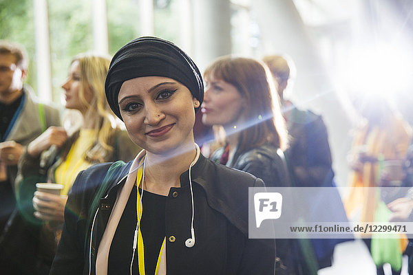 Portrait smiling woman in headscarf at conference