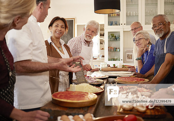 Senior friends listening to chef in pizza cooking class