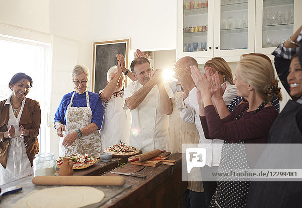 Chef and active senior friends clapping in pizza cooking class