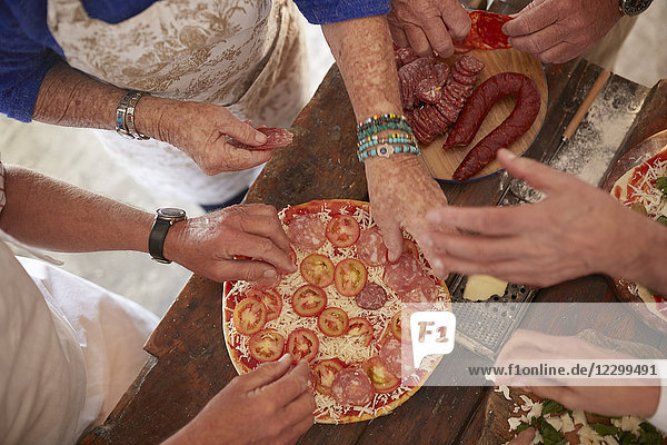 Overhead view senior friends adding tomatoes and meat to fresh pizza