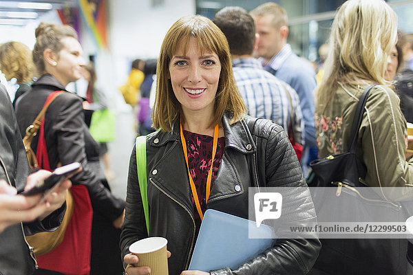 Portrait smiling  confident businesswoman drinking coffee at conference