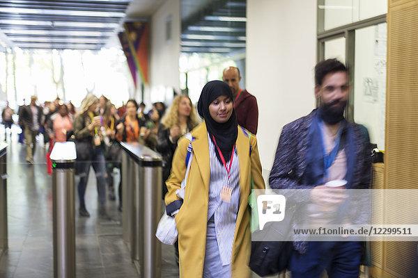 People arriving  entering turnstile at conference