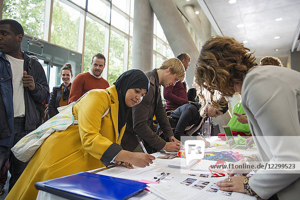 Businesswoman in hijab arriving  checking in at conference registration table