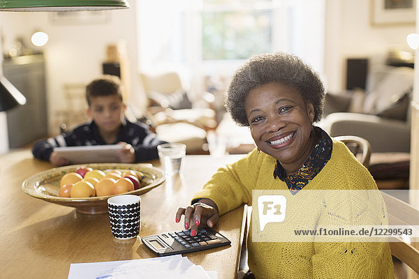 Portrait smiling senior woman paying bills at dining table