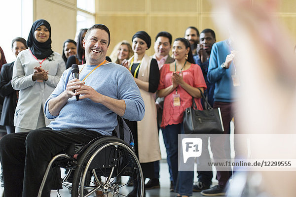 Audience clapping for male speaker in wheelchair