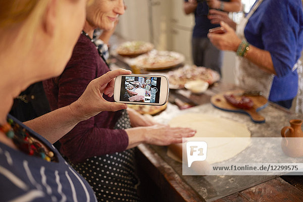 Woman with camera phone photographing friend making pizza dough in cooking class